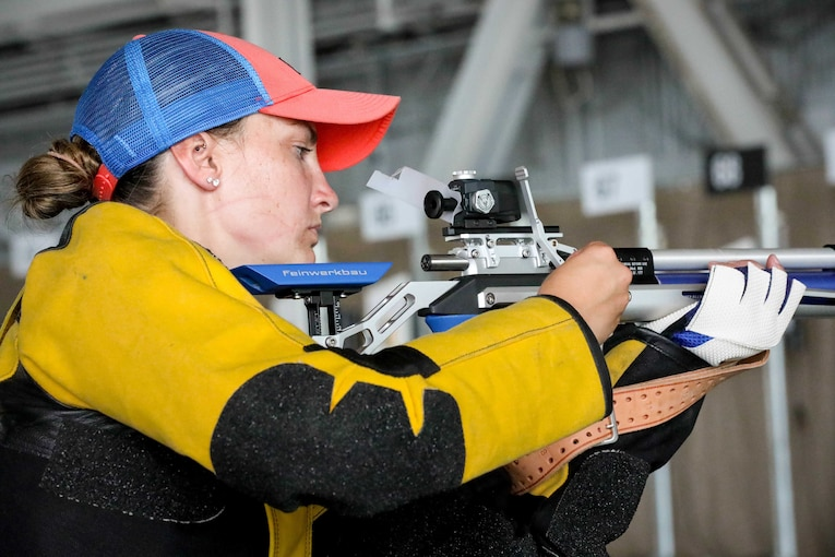 A soldier wearing a jacket and a ball cap loads a rifle at a competition range.