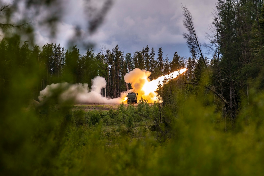 A rocket fired from behind a military vehicle that is surrounded by trees.