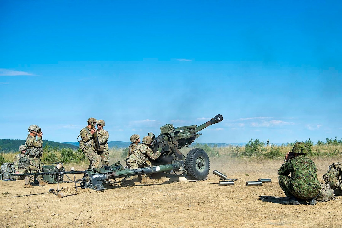 Soldiers fire a large military gun.