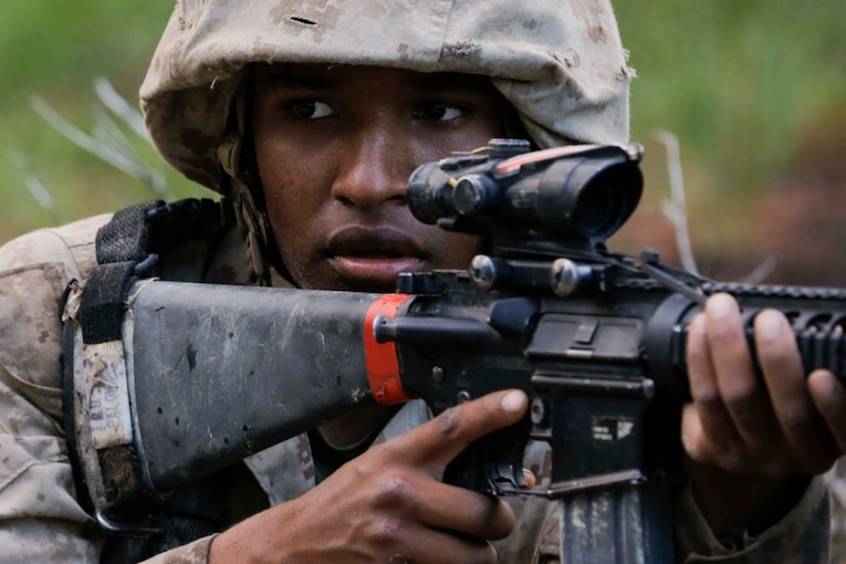 A Marine recruit holds a gun to his shoulder.