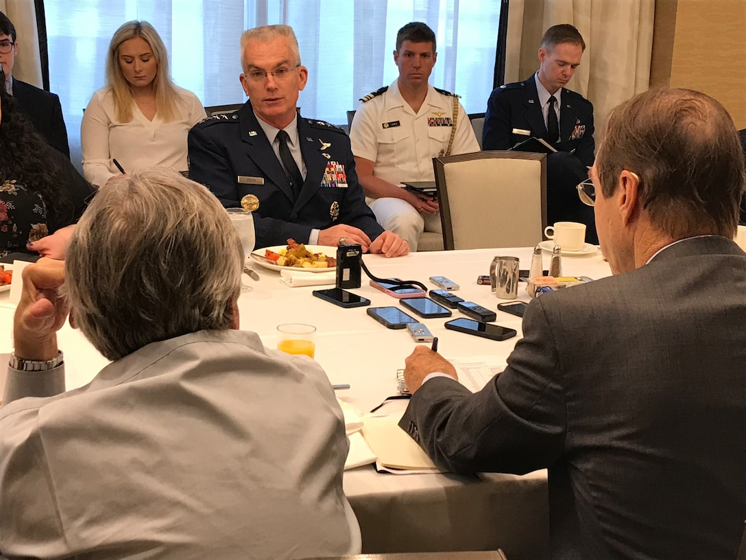 General speaks to a table full of reporters.