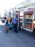 A family learns about the different features on a fire truck during a Navy Recruiting Command family picnic at the Defense Supply Center Columbus June 14. During the event, Fire and Emergency Services promoted fire safety and displayed a 100-foot ladder truck, personal protective gear and a variety of firefighter tools.