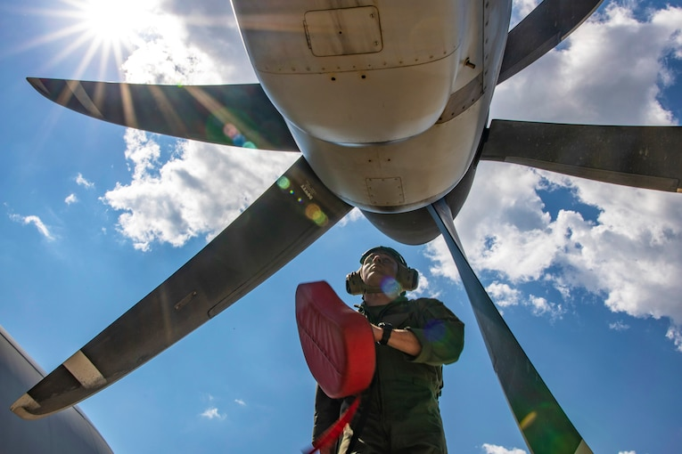 A Marine stands in front of a plane's propeller.