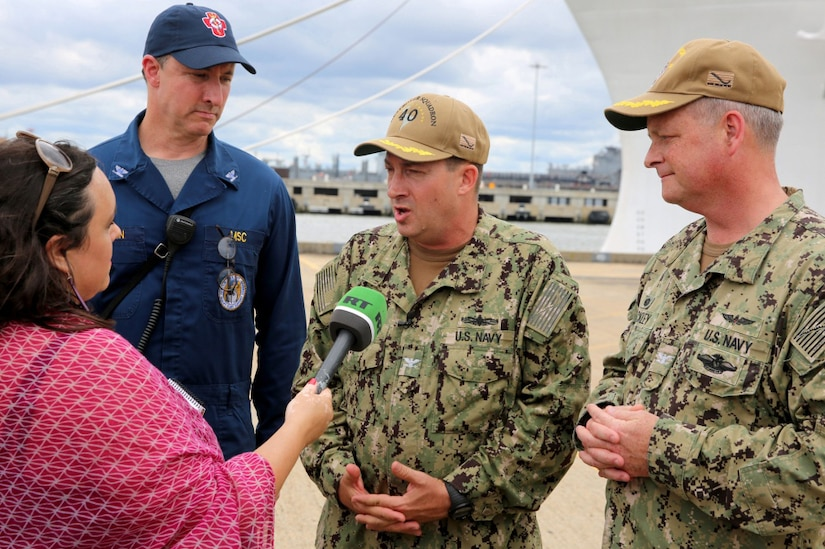 A reporter interviews three Navy officers in uniform.