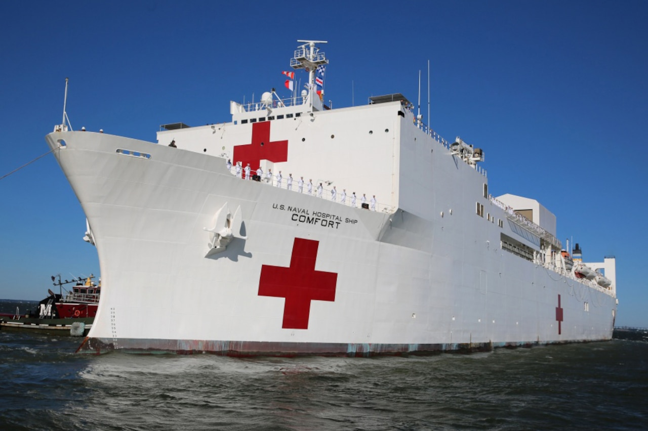 A white hospital ship with red cross markings moves through the water.