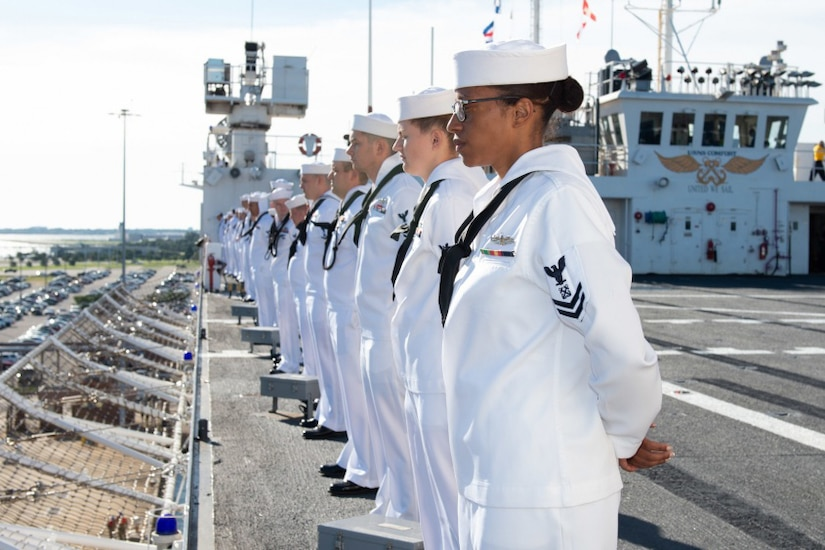 Sailors in white uniforms line the rail of a hospital ship.