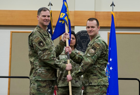 Capt. Daniel Evans, right, accepts command of the 841st Missile Security Forces Squadron from Col. Aaron Guill, 341st Security Forces Group commander, during a change of command ceremony June 18, 2019, at the Grizzly Bend on Malmstrom Air Force Base, Mont.