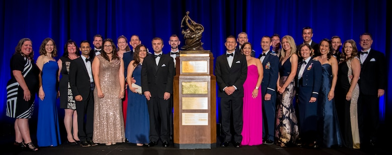 "Team Edwards poses for a picture next the Collier Trophy after the 2018 Robert J. Collier Trophy presentation ceremony, Washington, June 13, 2019. The Collier Trophy is awarded annually by the U.S. Aeronautic Association ""for the greatest achievement in aeronautics or astronautics in America, with respect to improving the performance, efficiency, and safety of air or space vehicles, the value of which has been thoroughly demonstrated by actual use during the preceding year.""(U.S. Air Force photo by Christopher Dyer)"