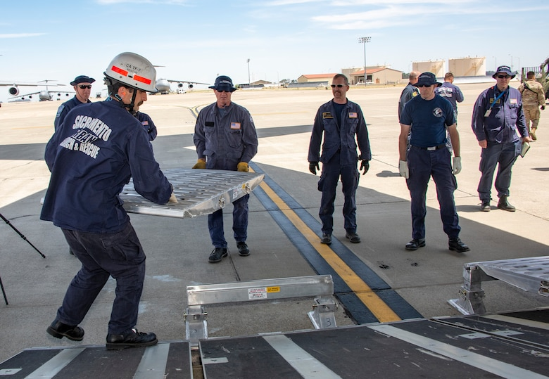 California Urban Search and Rescue Task Force 7 team members position vehicle ramps at the aft cargo bay door of a C-17 Globemaster III during a joint inspection and logistics drill conducted with 60th Aerial Port Squadron personnel June 13, 2019, at Travis Air Force Base, California. The annual training helps members of CA TF-7 learn about the process, governing and directives and ensures cargo is safe before loading onto an aircraft.  (U.S. Air Force photo by Heide Couch)