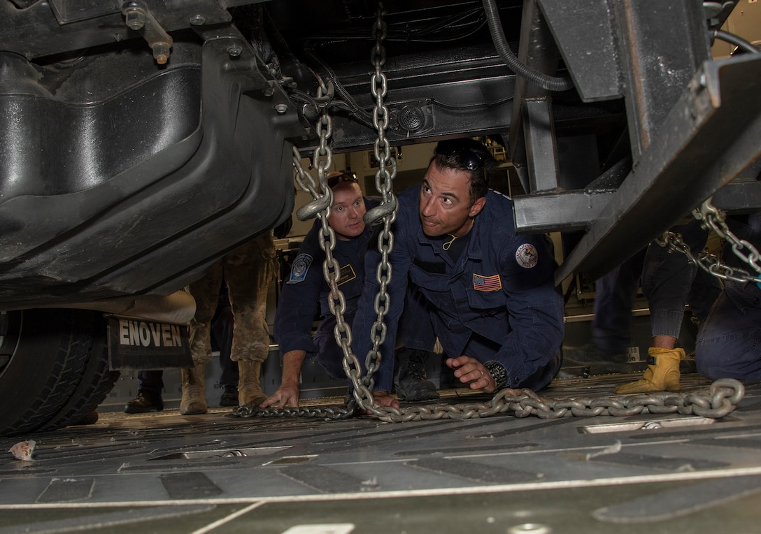 Liam McGregor, left, transportation manager and Matt Gonzales, California Urban Search and Rescue Task Force 7 transportation specialist, use a chain to secure an equipment transport trailer to the deck of a C-17 Globemaster III during a joint inspection and logistics drill conducted with 60th Aerial Port Squadron personnel June 13, 2019 at Travis Air Force Base, California. The annual training helps members of CA TF-7 learn about the process, governing and directives and ensures cargo is safe before loading onto an aircraft.  (U.S. Air Force photo by Heide Couch)