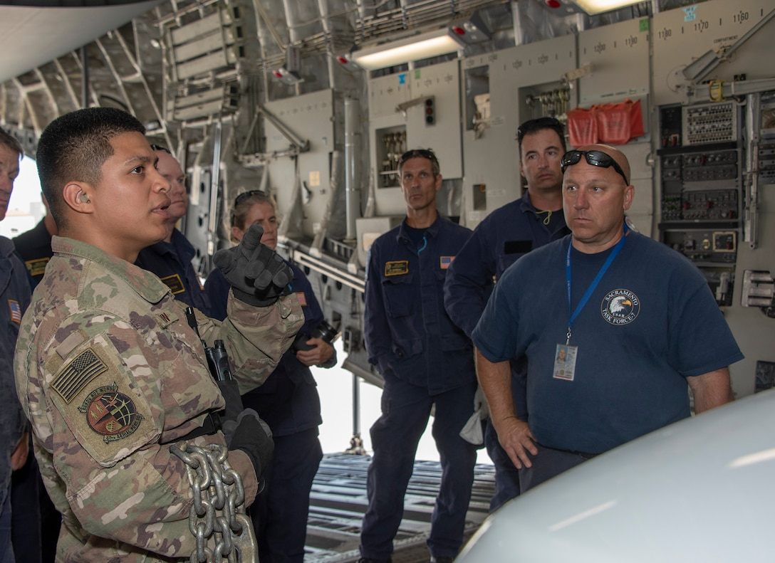 .S. Air Force Senior Airman Edward Colvin, left, a 60th Aerial Port Squadron expeditor, discuses cargo loading procedures with California Urban Search and Rescue Task Force 7 June 13, 2019 at Travis Air Force Base, California, during a joint inspection and logistics drill. The annual training helps members of CA TF-7 learn about the process, governing and directives and ensures cargo is safe before loading onto an aircraft.  (U.S. Air Force photo by Heide Couch)