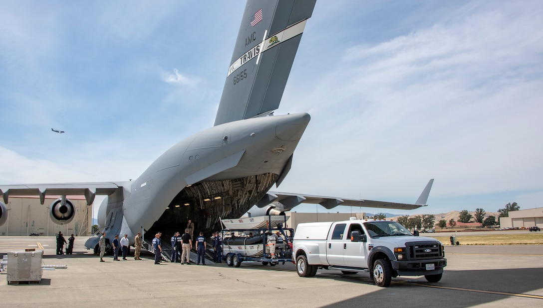 Members of California Urban Search and Rescue Task Force 7 and the 60th Aerial Port Squadron back a boat trailer into the cargo bay of a C-17 Globemaster III during a joint inspection and logistics drill June 13, 2019, at Travis Air Force Base, California. The annual training helps members of CA TF-7 learn about the process, governing and directives and ensures cargo is safe before loading onto an aircraft.  (U.S. Air Force photo by Heide Couch)