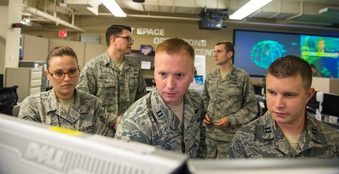 Airmen look at computer monitors.