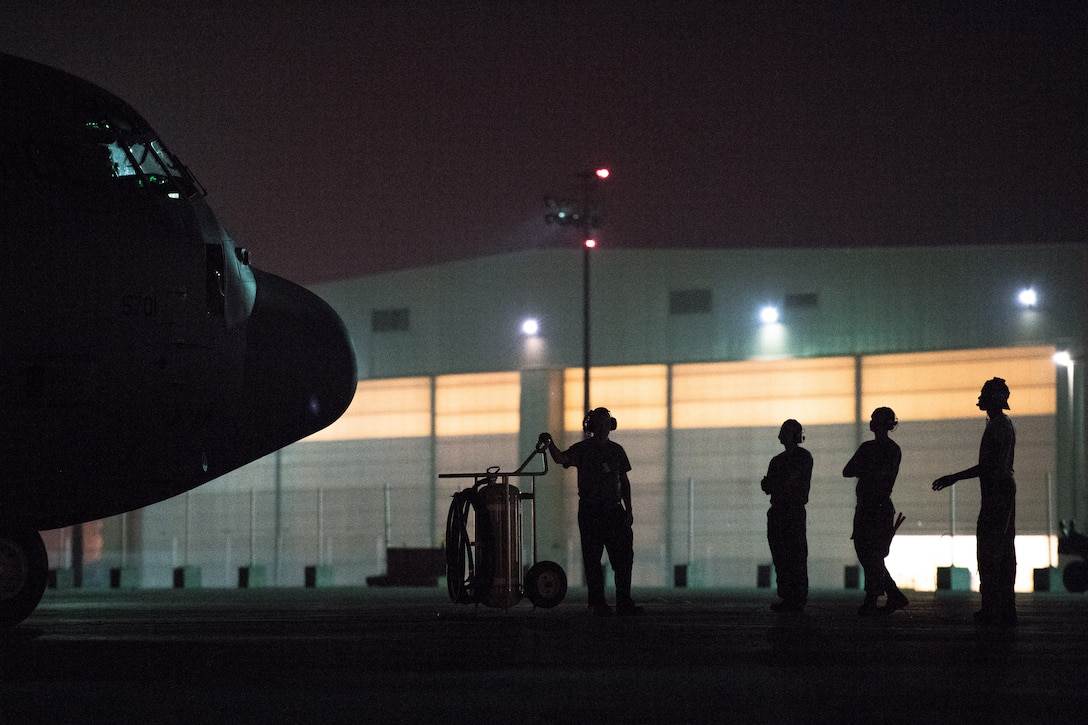 U.S. Air Force Airmen assigned to the 75th Expeditionary Airlift Squadron wait for further instruction before directing a C-130J Super Hercules on the flightline at Camp Lemonnier, Djibouti, June 5, 2019. The 75th EAS provides support in medical evacuations, disaster relief, humanitarian and airdrop operations. (U.S. Air Force photo by Staff Sgt. Devin Boyer)