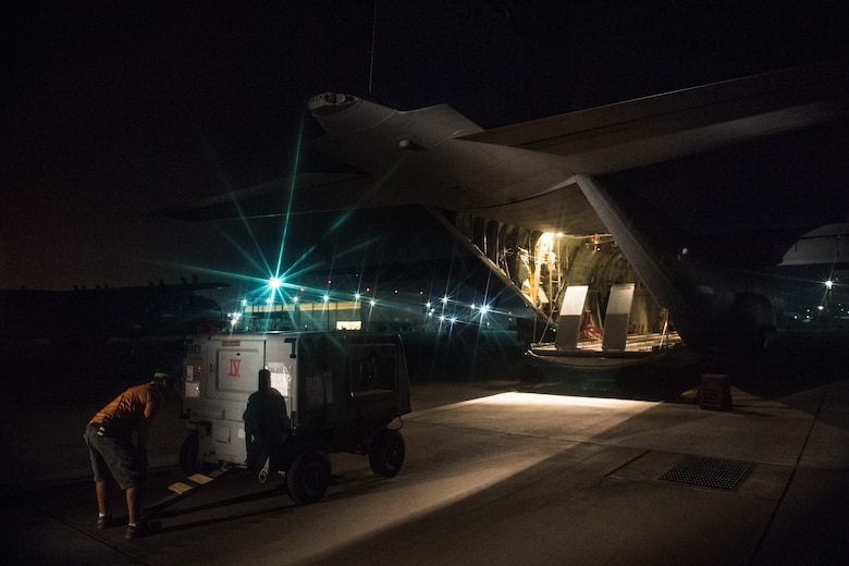 An air operations member prepares a generator before loading it onto a C-130J Super Hercules with the help of 75th Expeditionary Airlift Squadron Airmen at Camp Lemonnier, Djibouti, June 5, 2019. The 75th EAS provides support in medical evacuations, disaster relief, humanitarian and airdrop operations. (U.S. Air Force photo by Staff Sgt. Devin Boyer)