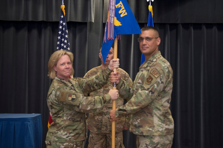 U.S. Air Force Col. Marlyce Roth, 52nd Mission Support Group commander, left, passes the ceremonial guidon to Lt. Col. Benjamin Washburn, incoming 52nd Security Forces Squadron commander, during the 52nd SFS change of command ceremony at Spangdahlem Air Base, Germany, June 18, 2019.