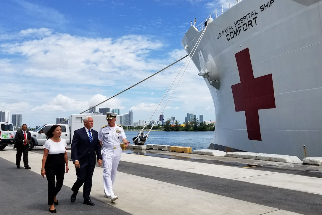Two men and a woman walk along the pier next to a hospital ship.