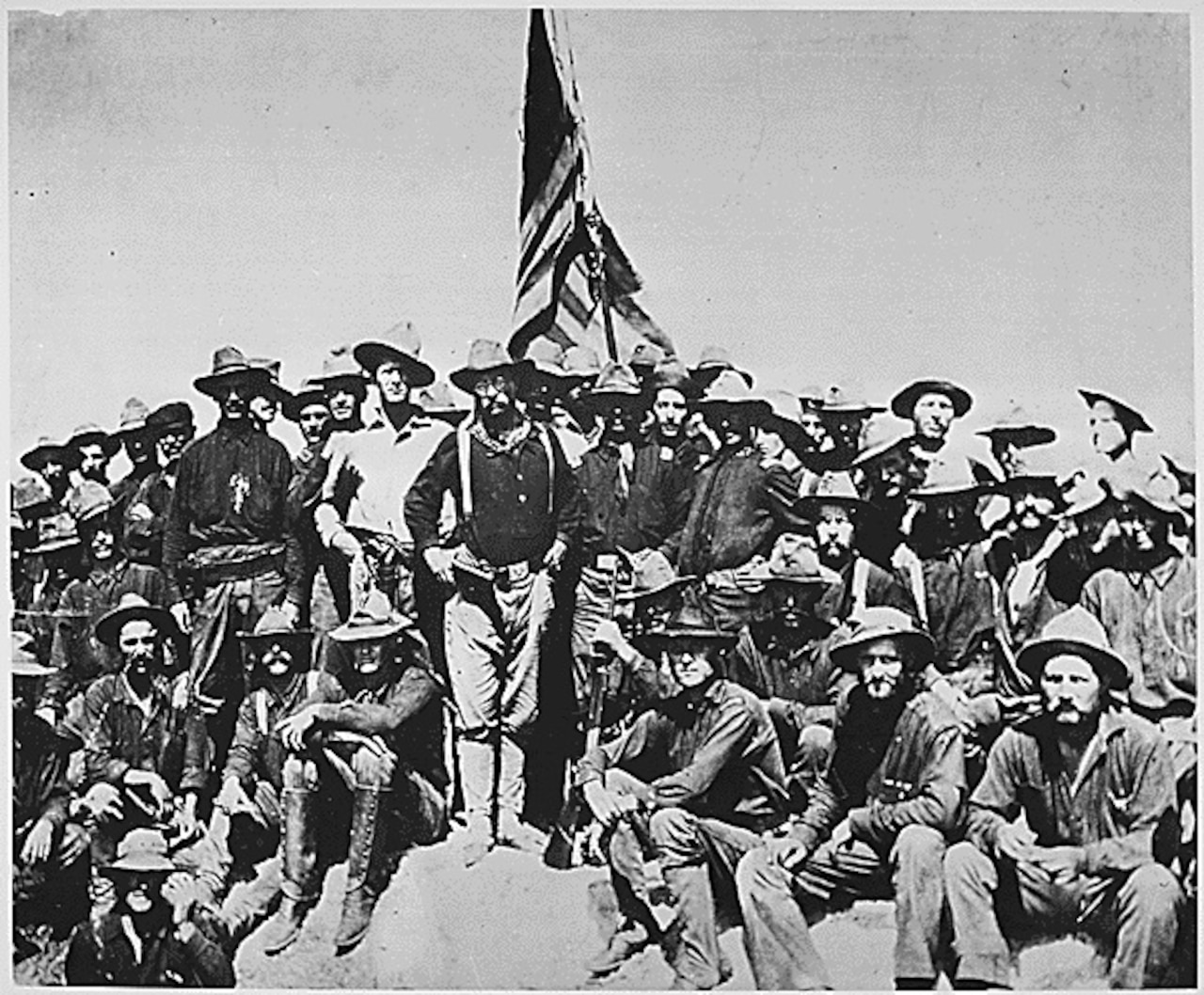 Several soldiers wearing wide-brimmed hats stand around a U.S. flag with then-Army Col. Theodore Roosevelt.