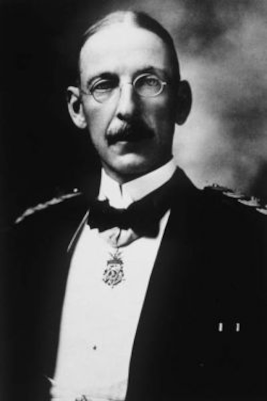 A man in 1800s-era suit and glasses poses with the Medal of Honor around his neck.