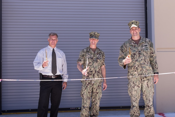 Norfolk Naval Shipyard dedicates its new Submarine Maintenance Facility June 14, consolidating submarine maintenance, production and support shops into a single facility adjacent to the shipyard's submarine drydocks and piers.  Participating in the ribbon-cutting from left to right are NNSY Submarine Program Manager Pat Ensley, Shipyard Commander Captain Kai Torkelson, and NAVFAC Public Works Officer Commander Ben Wainwright.