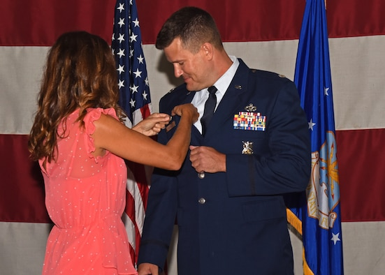 U.S. Air Force Lt. Col. Michael McCourt, incoming 312th Training Squadron commander, receives his commander's pin from his wife during the change of command ceremony at the Louis F. Garland Department of Defense Fire Academy High Bay on Goodfellow Air Force Base, Texas, June 19, 2019. The pin signifies that McCourt holds the position of commander of the squadron. (U.S. Air Force photo by Airman 1st Class Zachary Chapman/Released)