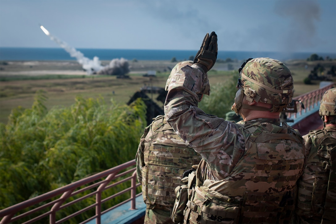 A soldier watches a missile fire.