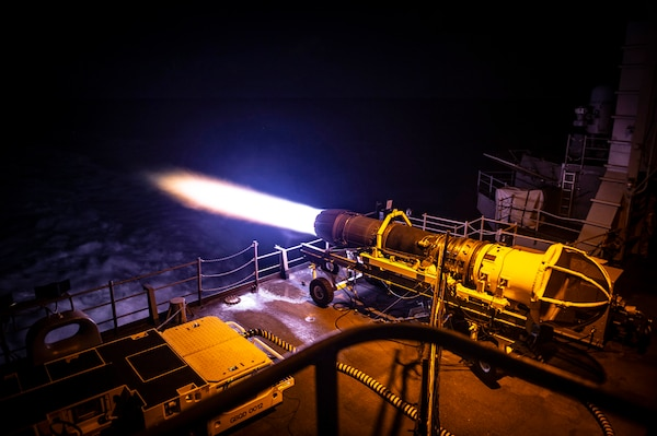 Flames spew from the back end of a jet cell being tested at night on an aircraft carrier.