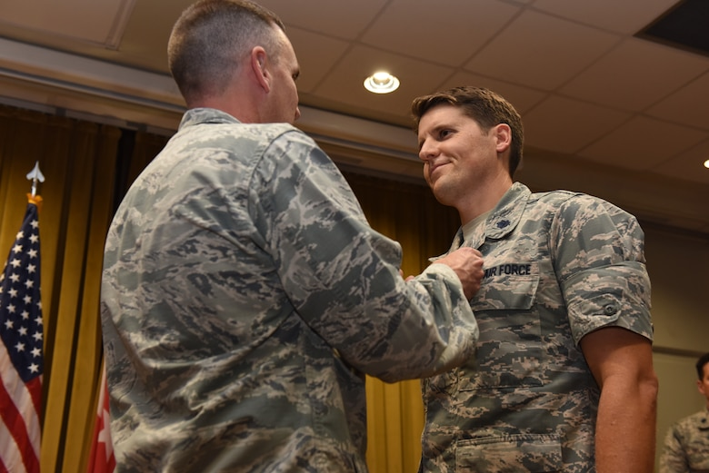Col. Christopher Estridge, 39th Medical Group commander, left, puts a Meritorious Service Medal on Lt. Col. Jason Telfer, 39th Medical Support Squadron commander, during the squadron's change of command ceremony on June 13, 2019, at Incirlik Air Base, Turkey. Telfer was awarded the medal for providing base operational support to two forward operating bases and 2,000 Airmen, enabling strategic airstrikes to the area of responsibility during his tenure as the 39th MDSS commander. (U.S. Air Force photo by Staff Sgt. Matthew J. Wisher)