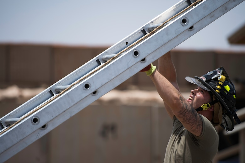 U.S. Air Force Senior Airman Logan Reed, 870th Air Expeditionary Squadron firefighter, throws a ladder at Chabelley Airfield, Djibouti, June 11, 2019. Firefighters must maintain top physical shape in order to perform their daily labor-intensive duties. (U.S. Air Force photo by Staff Sgt. Devin Boyer)