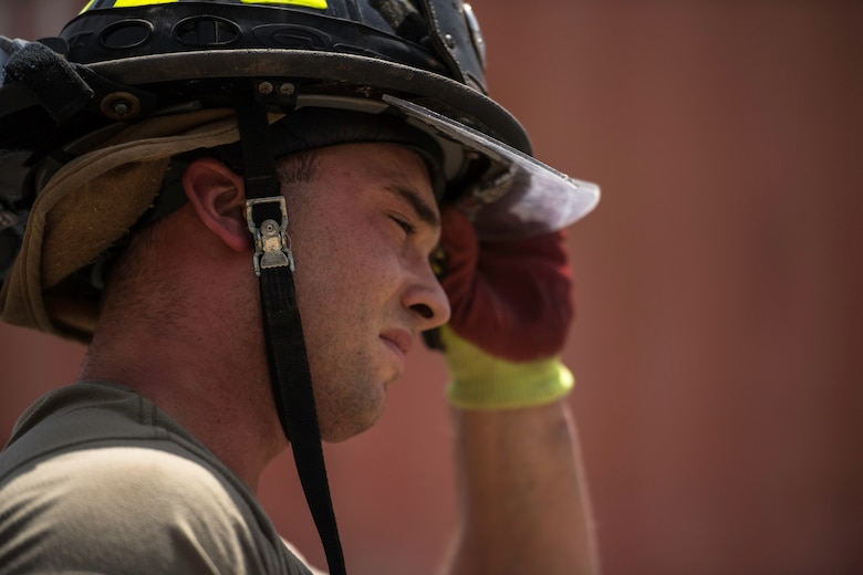 U.S. Air Force Senior Airman Logan Reed, 870th Air Expeditionary Squadron firefighter, adjusts his helmet at Chabelley Airfield, Djibouti, June 11, 2019. The 870th AES firefighters support the mission in East Africa by providing emergency services to the 449th Air Expeditionary Group and their assets. (U.S. Air Force photo by Staff Sgt. Devin Boyer)