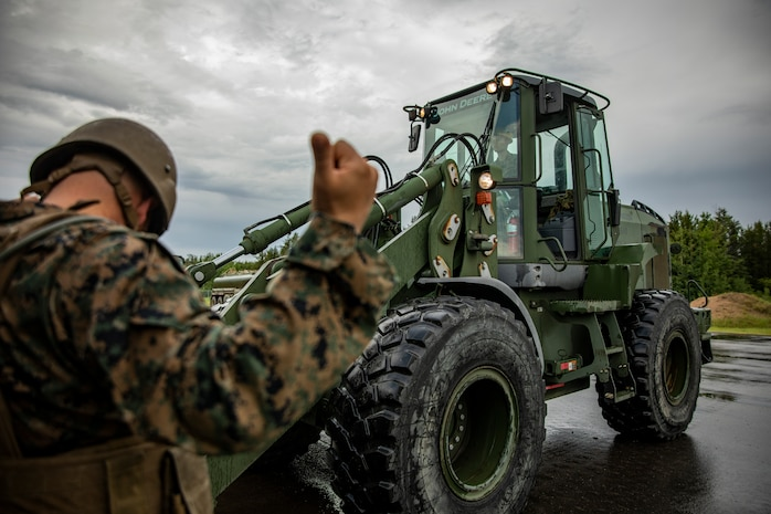 U.S. Marine Corps Cpl. Ryan Donnelly, right, a heavy equipment operator with Marine Wing Support Squadron 471, Marine Aircraft Group 41, 4th Marine Aircraft Wing, operates a tractor at Canadian Forces Base Cold Lake, Canada, June 19, 2019, in support of Sentinel Edge 19. Training exercises, such as SE19, ensure Reserve Marines are proficient and capable of successful integration with active-duty Marines, making MARFORRES critical to the Marine Corps' Total Force. (U.S. Marine Corps photo by Lance Cpl. Jose Gonzalez)