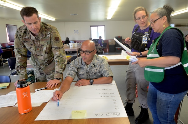 Oregon Air National Guard Capt. Kevin Lindsey , left, along with Capt. Vincent Faustino and State Emergency Registry of Volunteers in Oregon (SERV-OR) discuss strike and recovery teams during Pathfinder Exercise 2019, June 13, 2019, at Camp Rilea, Warrenton, Oregon.
