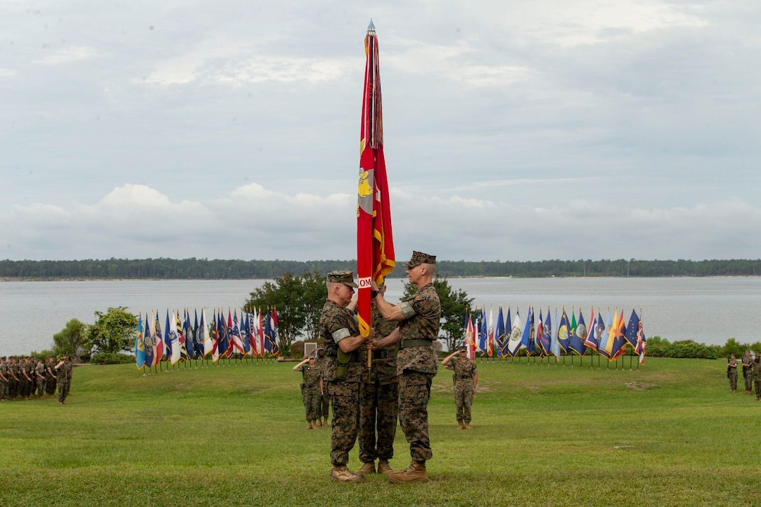 U.S. Marine Corps Col. Brian Mullery with Combat Logistics Regiment 27, 2nd Marine Logistics Group (left), receives the unit colors from Col. Boyd Miller with CLR-27, 2nd MLG (Right), during a change of command ceremony at Camp Lejeune, North Carolina, June 19, 2018. During the change of command Col. Boyd Miller relinquished command of CLR-27 to Col. Brian W. Mullery.   (U.S. Marine Corps photo by Cpl. Damion Hatch Jr.)