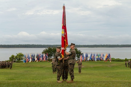 U.S. Marine Corps Col. Brian Mullery with Combat Logistics Regiment 27, 2nd Marine Logistics Group (left), receives the unit colors from Col. Boyd Miller with CLR-27, 2nd MLG (Right), during a change of command ceremony at Camp Lejeune, North Carolina, June 19, 2018. During the change of command Col. Boyd Miller relinquished command of CLR-27 to Col. Brian W. Mullery. 