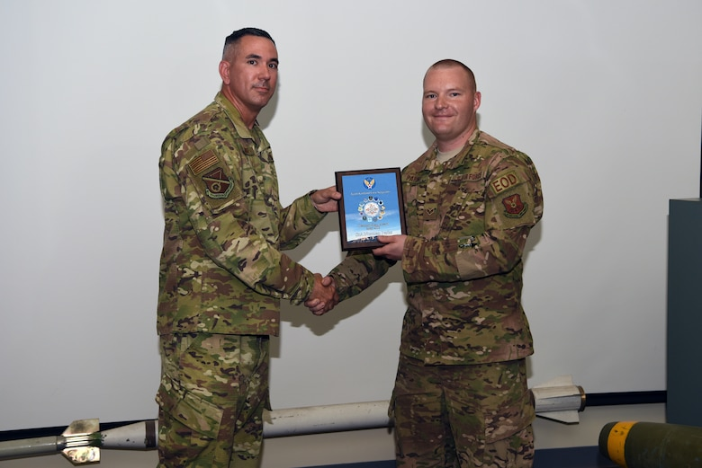 Senior Airman Norman Parks, 377th Civil Engineer Squadron explosive ordnance disposal technician, receives the May Diamond Sharp award from Master Sgt. Jason Meuse, 377th Mission Support Group first sergeant, at Kirtland Air Force Base, N.M., June 19, 2019. Parks used existing spare parts to create a new attachments for the EOD robots, and the new attachment has been implemented throughout the Air Force. Parks was also awarded Senior Airman Below the Zone. (U.S. Air Force photo by Senior Airman Eli Chevalier)