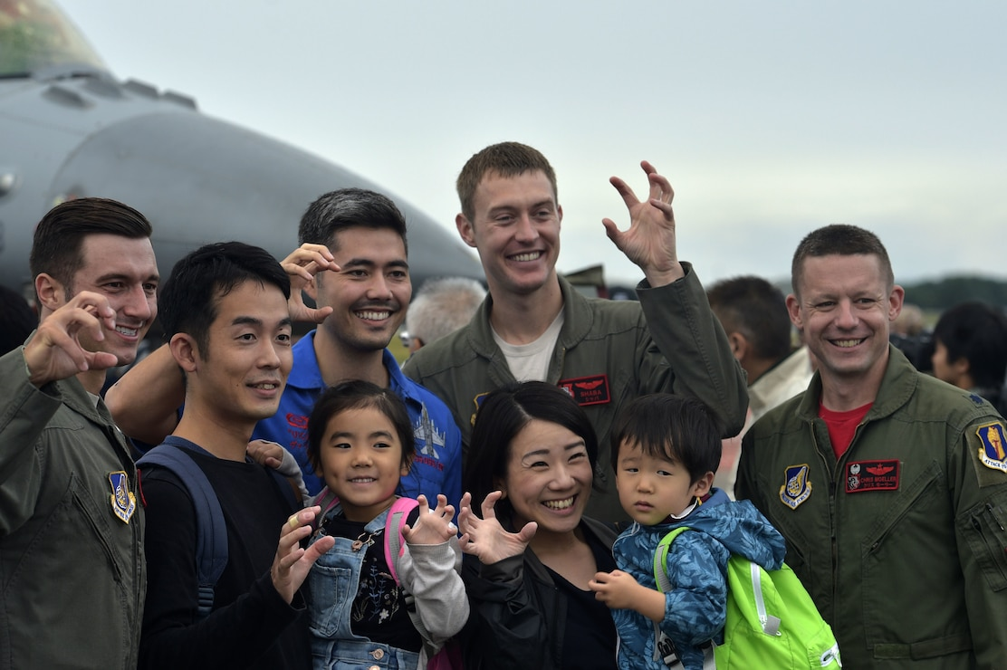 Pilots with the 13th Fighter Squadron pause for photographs with Japanese nationals during the Misawa Friendship Festival 2018 at Misawa Air Base, Japan, Sept. 9, 2018. The festival featured more than 15 aircraft displays, 60 vendors and multiple ground demonstrations throughout the day.