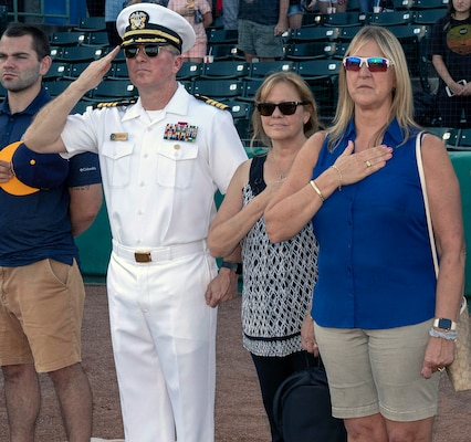 (From left) Capt. Timothy Richardson, deputy commander of Navy Medicine Education, Training and Logistics Command, or NMETLC, his wife Sandi Richardson and Gail Hathaway, associate chief of staff for NMETLC, salute during the national anthem during a San Antonio Missions baseball team, after throwing out the first pitch in honor of military appreciation night.