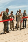 U.S. Marine Corps Sgt. Jacob R. Mott, rifleman, 3rd Battalion, 4th Marine Regiment, 1st Marine Division, cuts the ribbon to celebrate the re-opening of Range 105A, Marine Corps Air Ground Combat Center, Twentynine Palms, Calif., Jun 17, 2019. The range was re-designed to offer multiple, efficient types of training to individual Marines and squad-sized elements. (U.S. Marine Corps photo by Pfc. Gustavo Romero)