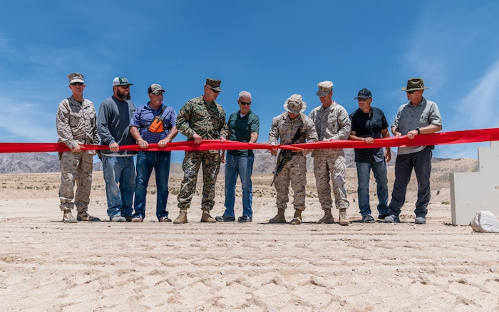 U.S. Marines and Department of Defense contractors take part in the ribbon cutting ceremony for the re-opening of Range 105A at Marine Corps Air Ground Combat Center, Twentynine Palms, Calif., June 17, 2019. The range was re-designed to offer multiple, efficient types of training to individual Marines and squad-sized elements. (U.S. Marine Corps photo by Cpl. Rachel K. Young-Porter)