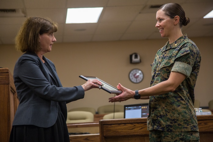 Marci Jensen-Eldred (left), chief attorney, San Bernardino County Child Support Services, presents a certificate of appreciation to Maj. Kerry E. Friedewald, legal assistant officer in charge, Legal Service Support Team, Headquarters Battalion, Marine Corps Air Ground Combat Center (MCAGCC) at MCAGCC, Twentynine Palms, Calif., June 18, 2019. The section was awarded a certificate of appreciation for their work with the San Bernardino County Child Support Services.  (U.S. Marine Corps photo by Cpl. Francisco J. Britoramirez)