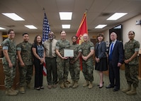 Marines with Legal Services Support Team, Headquarters Battalion, Marine Corps Air Ground Combat Center (MCAGCC), display a certificate of appreciation given by members of the San Bernardino County Child Support Services at MCAGCC, Twentynine Palms, Calif., June 18, 2019. The section was awarded a certificate of appreciation for their work with the San Bernardino County Child Support Services.  (U.S. Marine Corps photo by Cpl. Francisco J. Britoramirez)