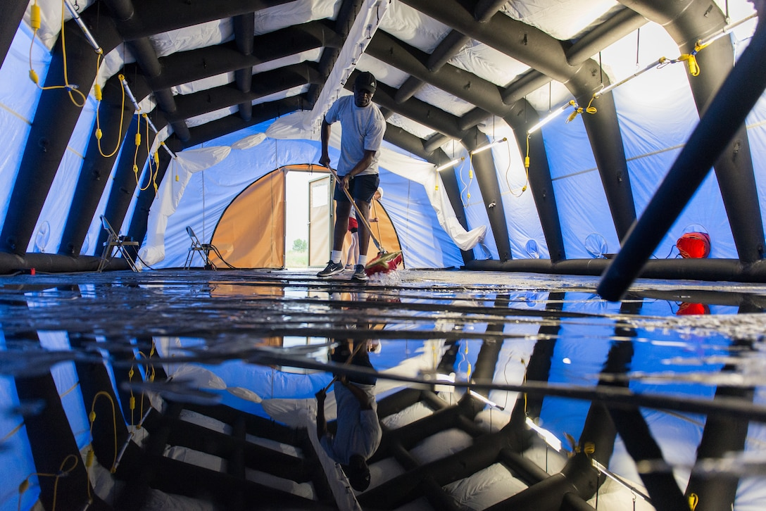 A biomedical equipment technician removes water from a flooded inflatable air shelter