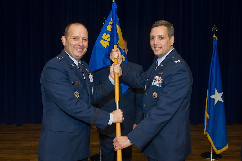 Brig. Gen. Douglas Shiess, 45th Space Wing commander, presents Col. Edward Marshall, incoming 45th Mission Support Group commander, with the 45th MSG guidon as he assumes command of the squadron. (U.S. Air Force photo by Jared Trimarchi)