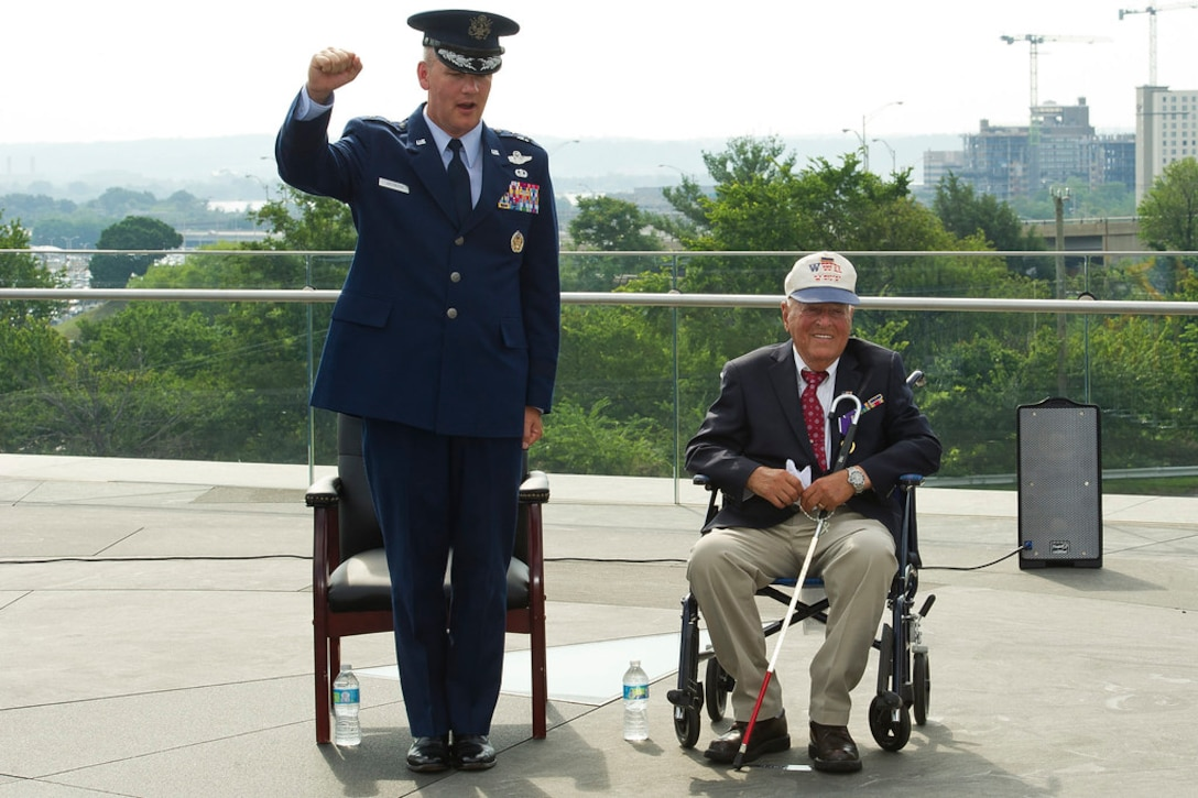 ARLINGTON, Va. --Maj. Gen. James Jacobson, Air Force District of Washington commander, and 2nd Lt. John Pedevillano sing the Air Force song  following a Purple Heart presentation ceremony in Pedevillano�s honor at the Air Force Memorial, Jul. 14, 2017.  Pedevillano, a B-17 bombardier pilot, received the award for wounds he incurred during a forced march as a World War II prisoner of war.  Pedevillano also received tokens of appreciation from both the Secretary and Chief of Staff of the Air Force.