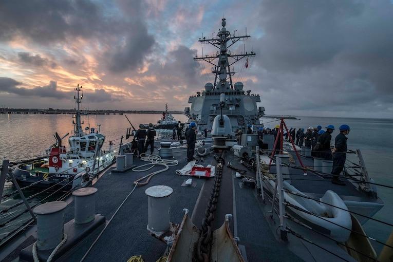 A military ship sets sail as the sun sets behind it.
