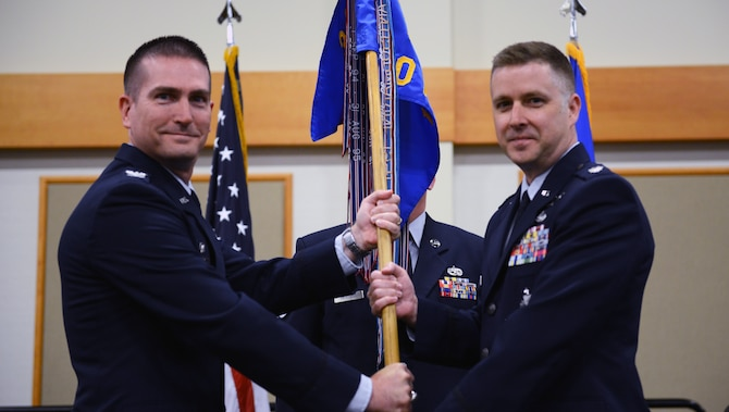 Lt. Col. Jeffrey Regan, right, accepts command of the 10th Missile Squadron from Col. Christopher Menuey, 341st Operations Group commander, during a change of command ceremony June 20, 2019, at the Grizzly Bend on Malmstrom Air Force Base, Mont. Guidon bearer Master Sgt. Brook Mertens, 10th MS facility manager, looks on. (U.S. Air Force photo by Staff Sgt. Magen M. Reeves)