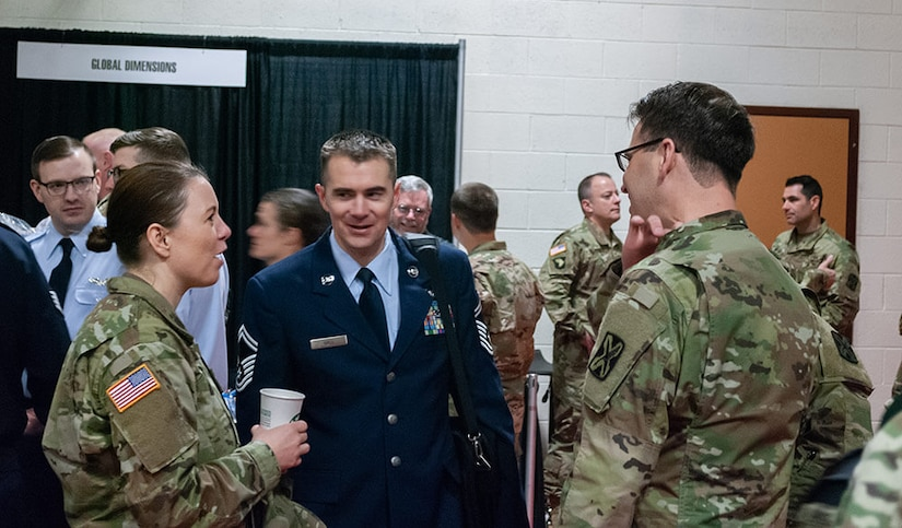 Left to Right: SSG Rose Bowman, 142nd Military Intelligence Battalion, Utah Army National Guard; SMSgt Jacob Hall, 169th Intelligence Squadron, Utah Air National Guard; and SSG Thomas Good, 142nd Military Intelligence Battalion, Utah Army National Guard, mingle during the expo portion of the 300th Military Intelligence Brigade's 30th Annual Language Conference