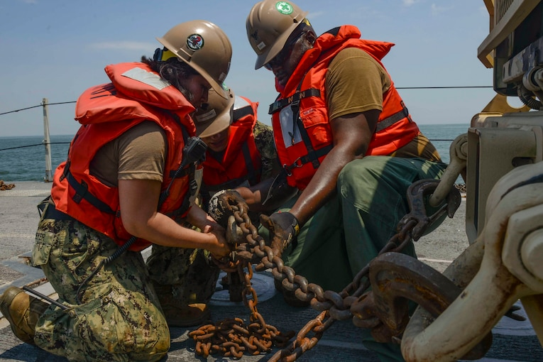 Three sailors use a metal chain to secure a vehicle to the floor.