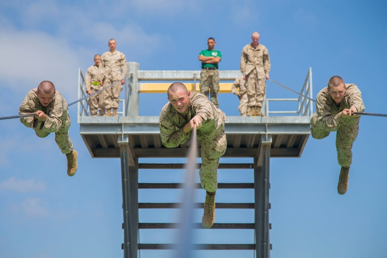 Three Marines slide along a rope suspended high above the ground as other Marines watch and wait.