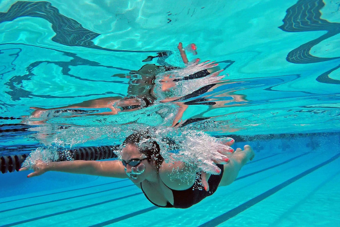 A sailor wearing goggles swims underwater, spreading her arms forward.